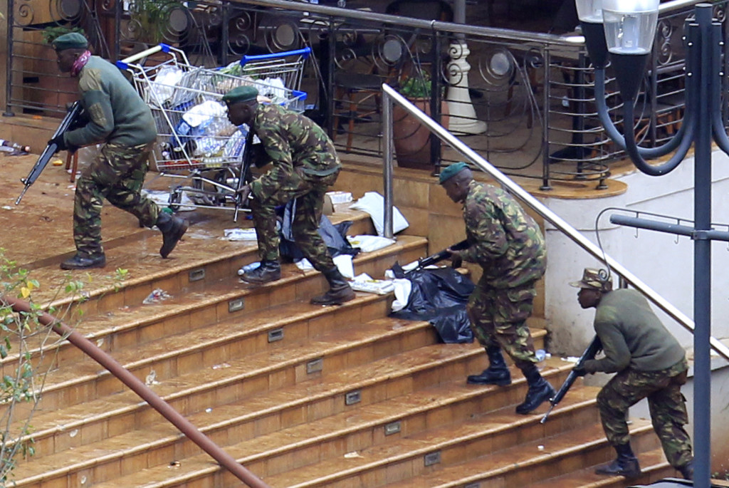 "Kenya Defence Forces soldiers take their position at the Westgate shopping centre, on the fourth day since militants stormed into the mall, in Nairobi September 24, 2013. Somalia's al Shabaab Islamist group said on Tuesday there were ""countless dead bodies"" in the Westgate shopping centre as security forces searched for militants still holed up in the complex after a weekend attack that authorities say killed 62 people. REUTERS/Noor Khamis (KENYA - Tags: CIVIL UNREST CRIME LAW MILITARY) - RTX13XFO"